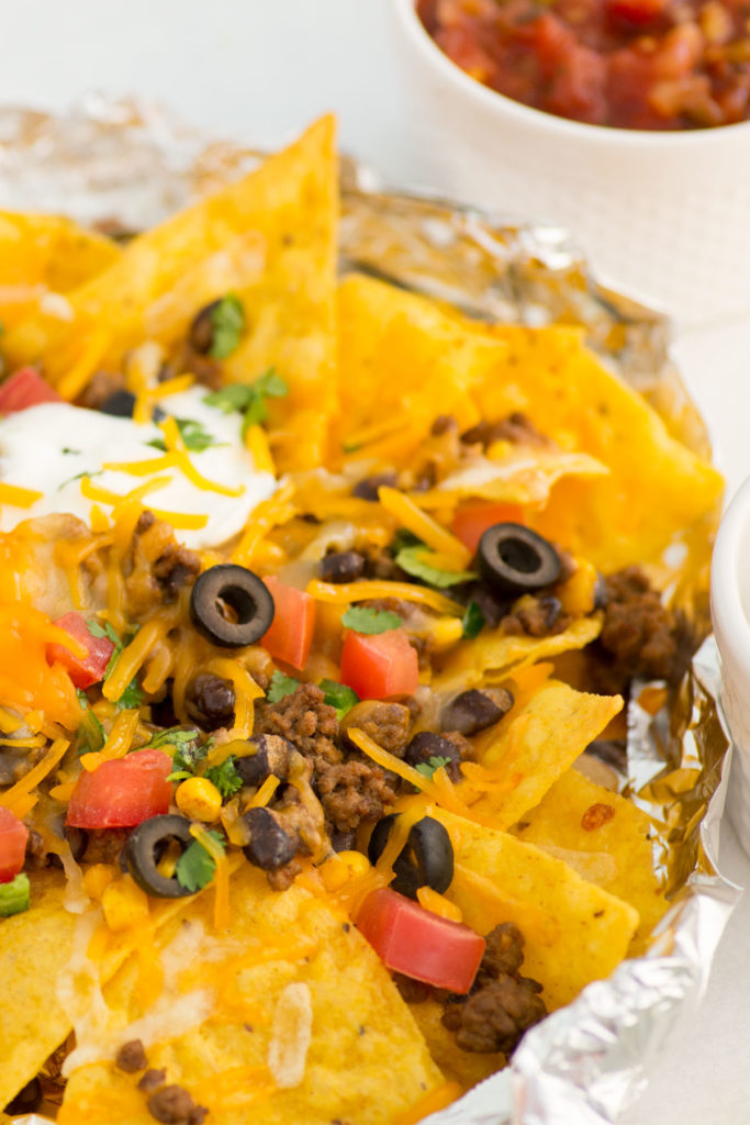 Nachos in a foil packet with small bowls of salsa next to it.