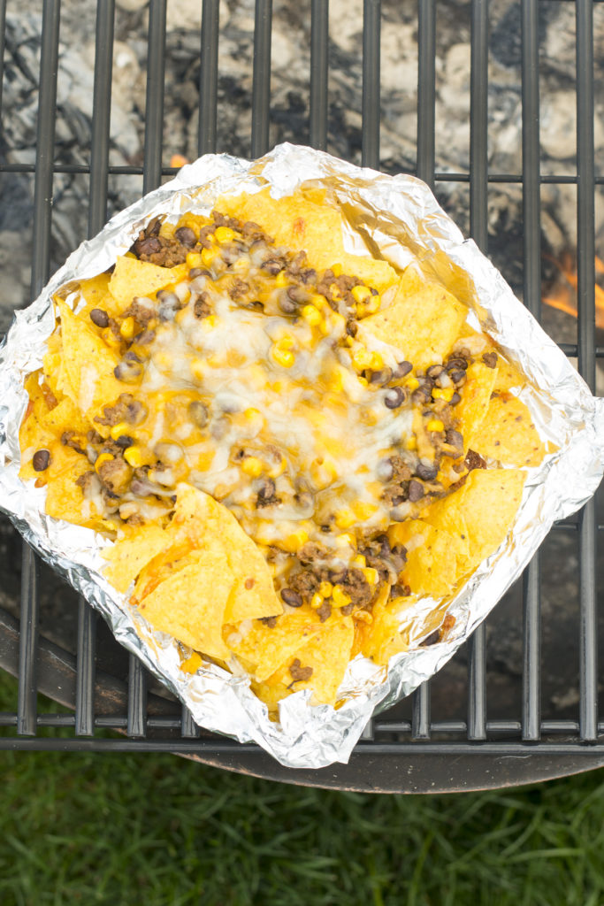 Nachos in a foil packet over a campfire sitting on a grate.