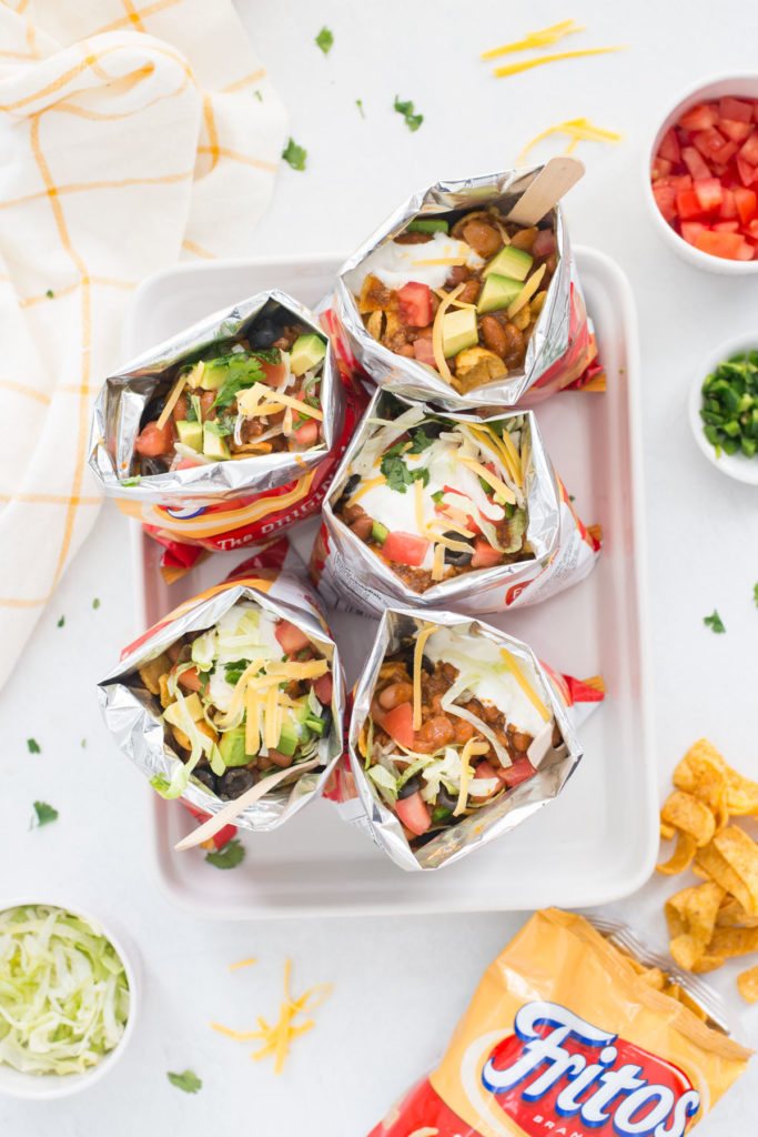 5 bags of walking tacos on a white platter with white bowls filled with lettuce, tomatoes, green onions around it with an open bag of Fritos next to it.
