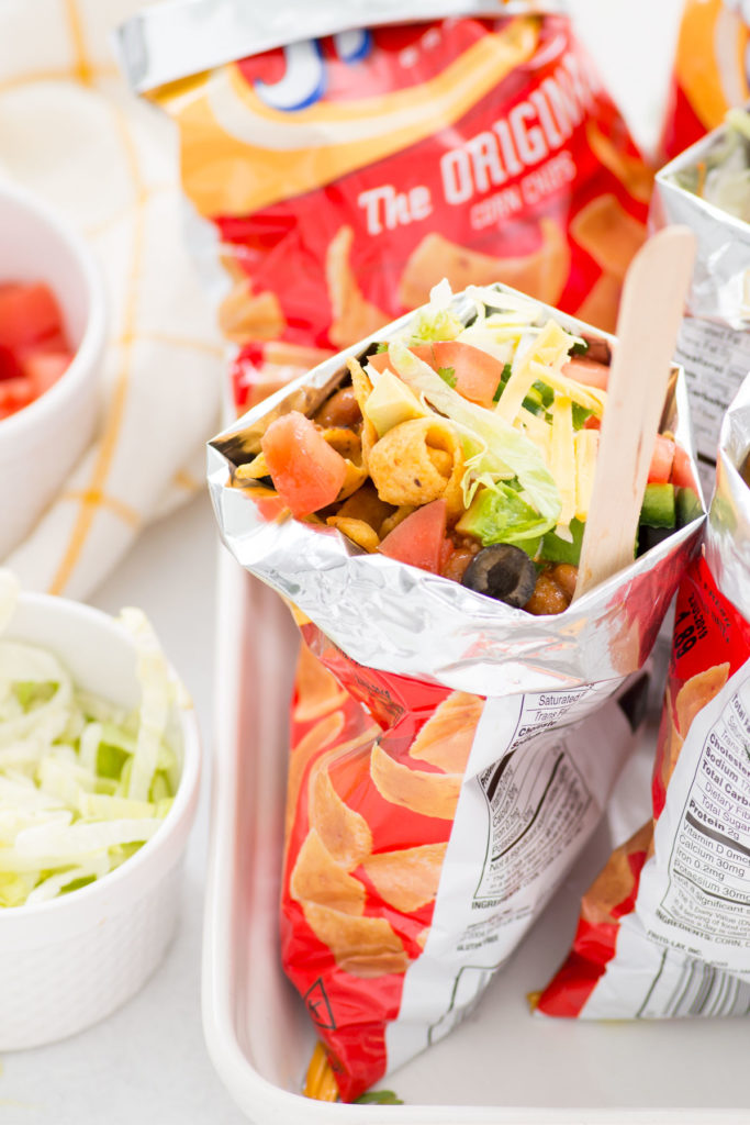 Bags of walking tacos with a wooden spoon on a white platter with white bowls filled with lettuce and tomatoes.