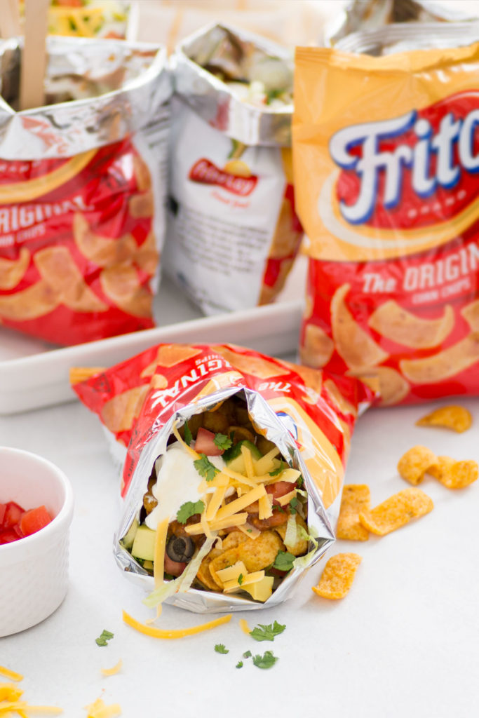 2 bags of frito bandito walking tacos on a white platter and an another bag of walking tacos laying down open with fritos on the counter with a white bowl filled with cut tomatoes also on the side.