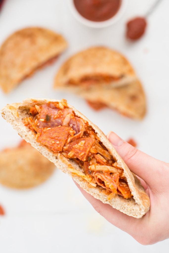 A hand is holding a pizza pita pocket close up while there are four pizza pita pockets below on white background and a small white bowl and spoon filled with tomato sauce.