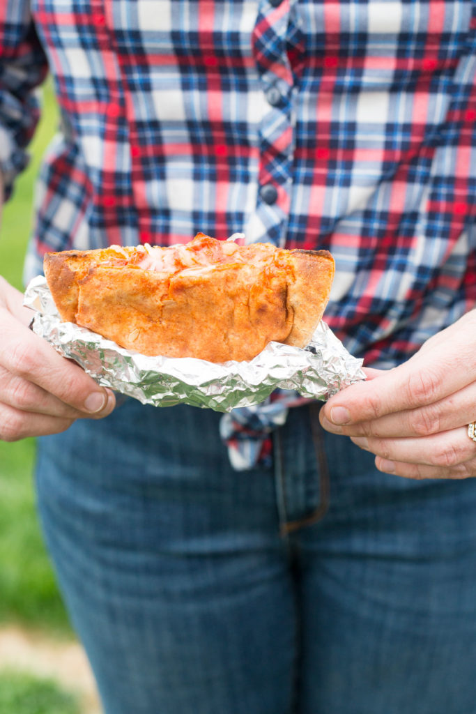 A body wearing jeans and a plaid shirt with two hands holding a pizza pocket in foil in front.