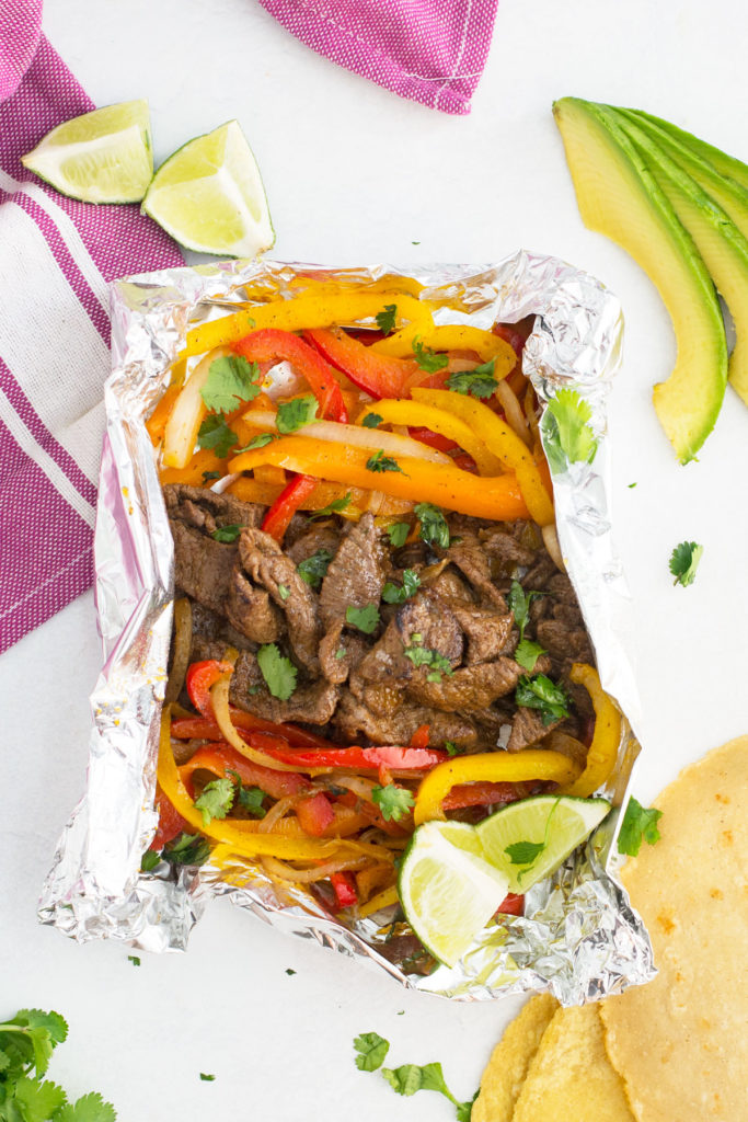 There is a foil packet with fajita toppings under a pink and white towel with cut up limes, cut up avocados and plain tortillas around it.