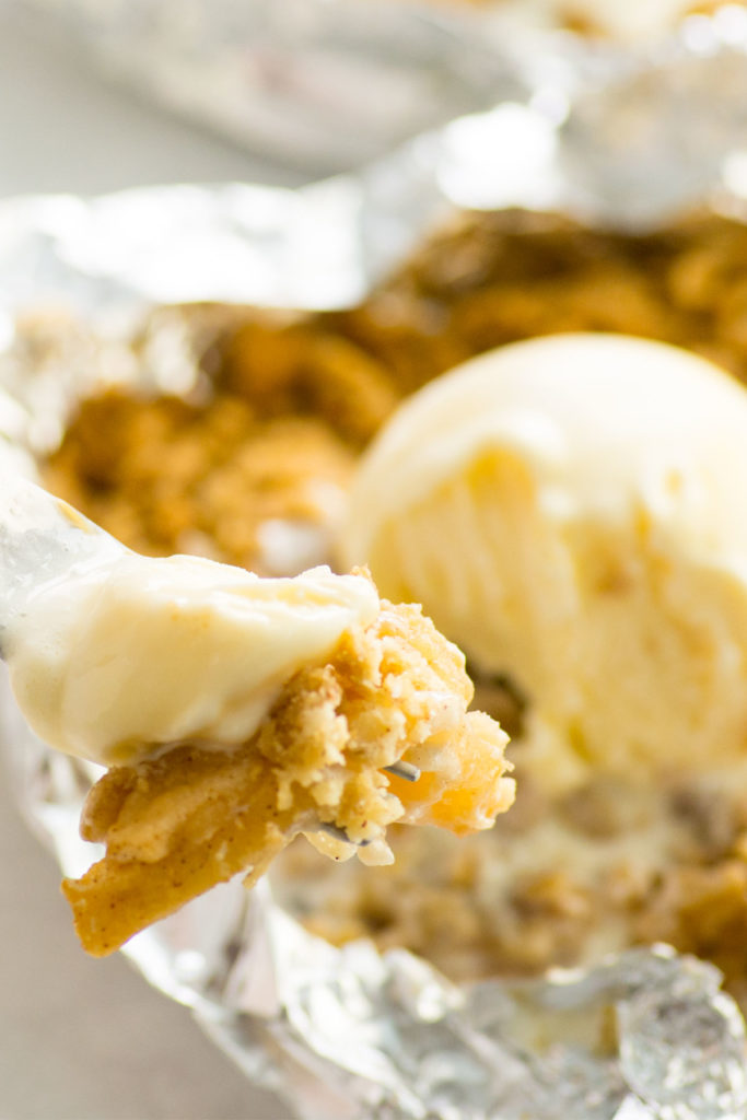 A foil packet filled with apple crisp with a scoop of ice cream with a fork with a apple crisp on it.