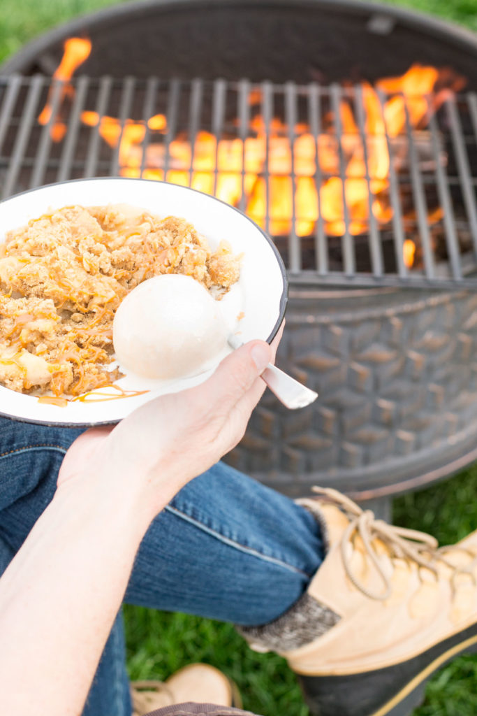 There is a campfire with a grate on it with a person holding a dish of warm apples and a cinnamon crumb topping with a scoop of ice cream on it.
