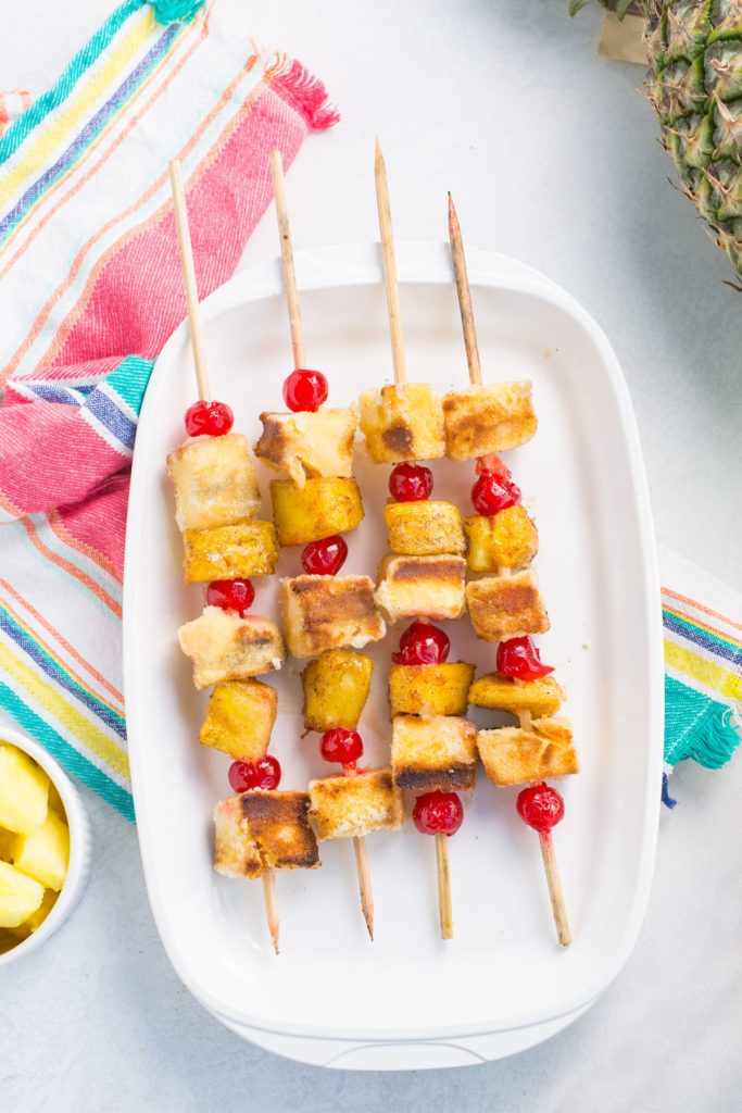 A white oval dish holding 4 pineapple upside down cake kabobs with a striped towel and a pineapple on the side with a small white bowl of cut pineapple on the side.