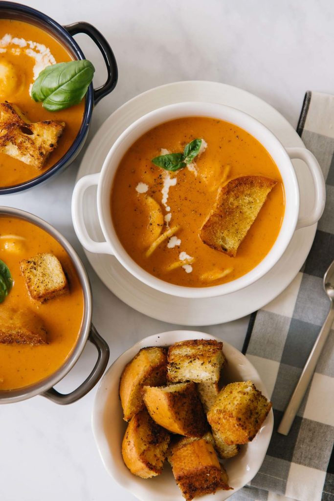 Creamy tomato basil soup in three bowls. Inside bowls of soup are basil, croutons, ravioli and a dripping of fresh cream to garnish.
