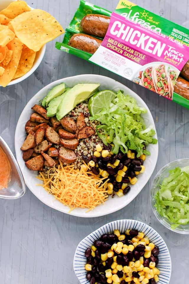 Quinoa burrito bowls with chicken sausage, avocado slices, lime, lettuce, cheese and black beans with corn.