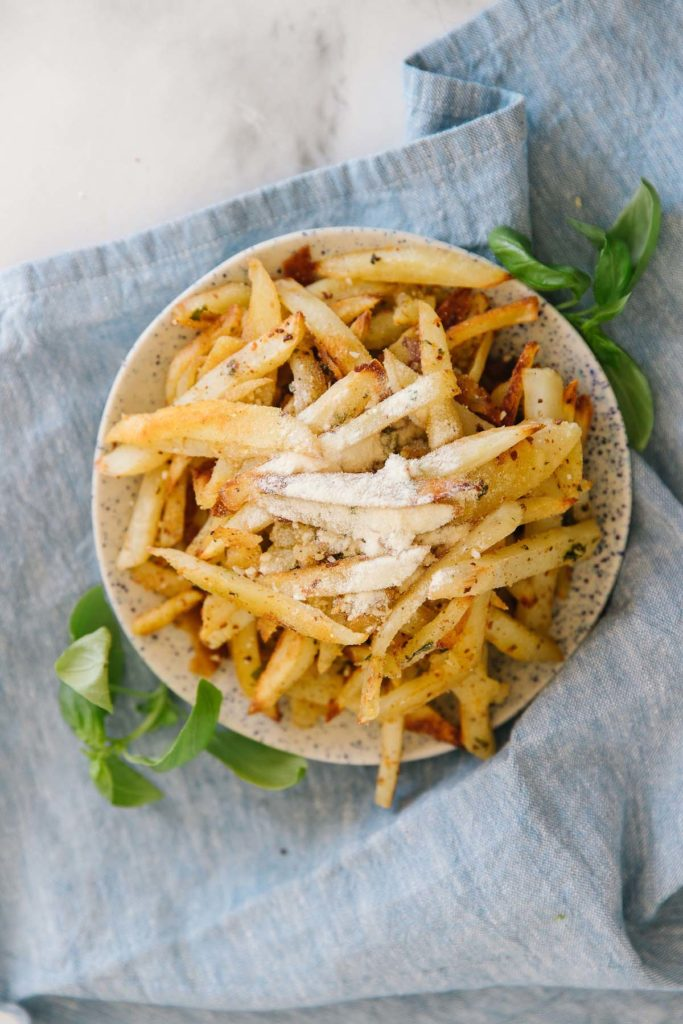A plate full of french fries with Parmesan cheese sprinkled on it with basil on the side on top of a blue tablecloth.