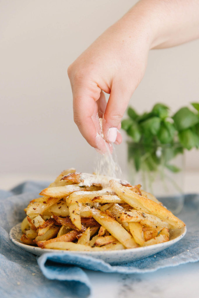 A plate full of french fries with a hand sprinkling Parmesan cheese on it with basil on the side on top of a blue tablecloth.