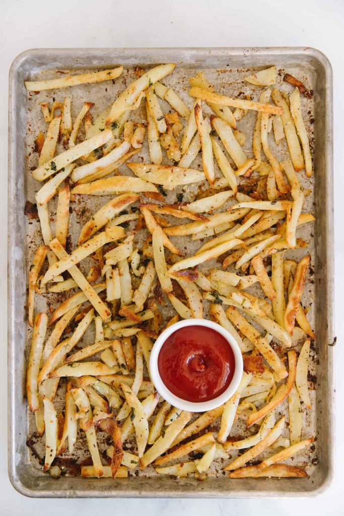 A cookie sheet filled with cooked cut potato slices sprinkled with seasonings and basil. There is a white bowl of ketchup in the bottom middle of the pan.
