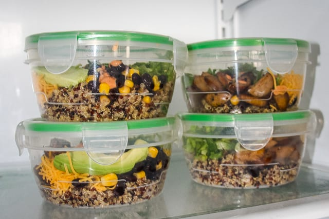 Four make ahead meal prep quinoa burrito bowls filled with Quinoa ,chicken sausage, avocado slices, lime, lettuce, cheese and black beans with corn.