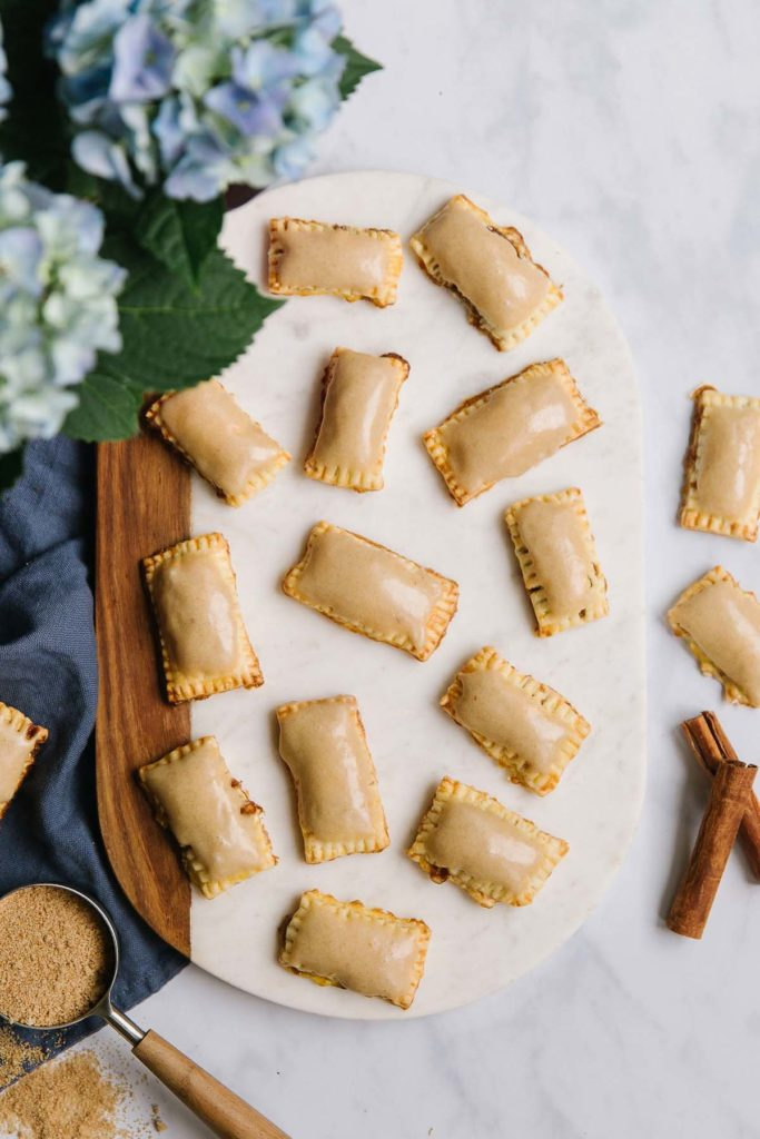 An oval wooden and white plate is holding pop tarts with brown icing on it with flowers, a cup of brown sugar and cinnamon sticks.