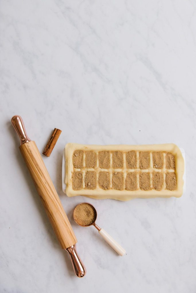 A wooden rolling pin with a copper measuring cup full of sugar next to an ice cube tray with a pie crust on top of it and each cube filled in with a brown sugar mixture.