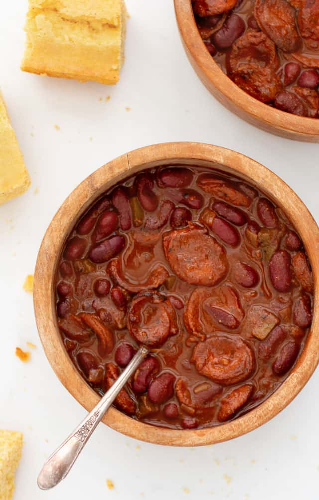 2 bowls of Red bean and sausage chili in wooden bowls and a few squares of cornbread and crumbs scattered around bowls.