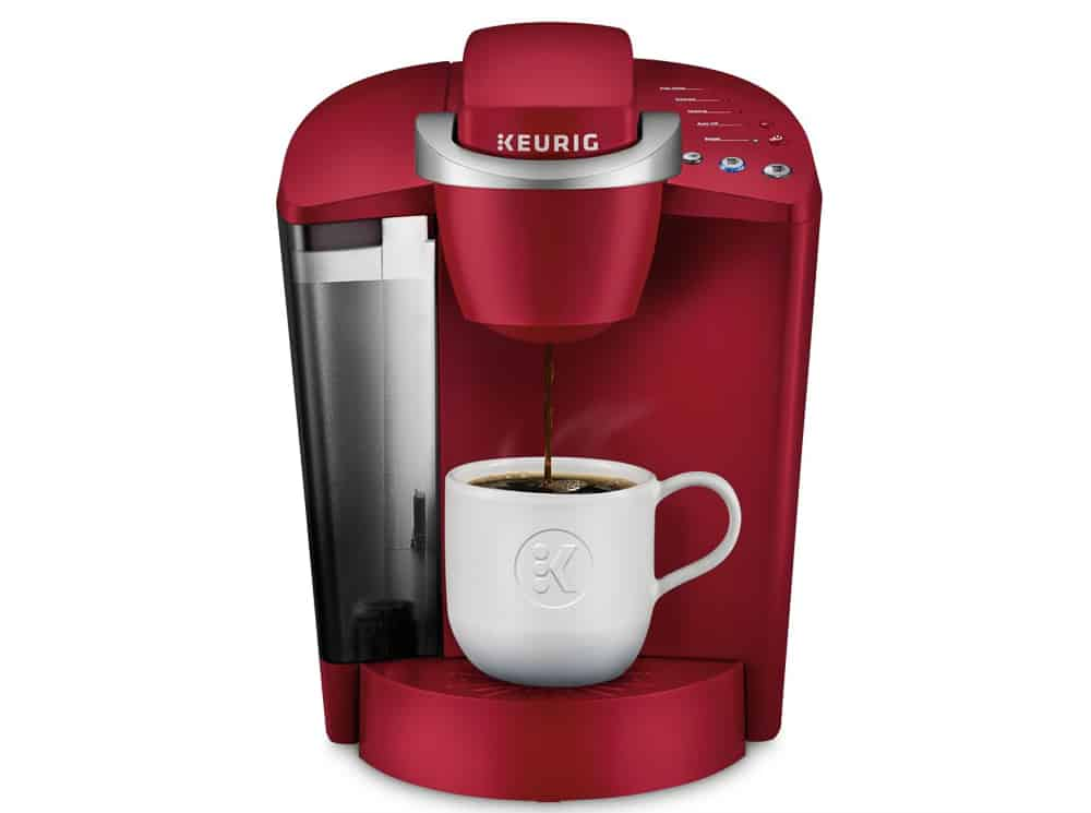Red Keurig Coffee Maker pouring cup of coffee into white cup.