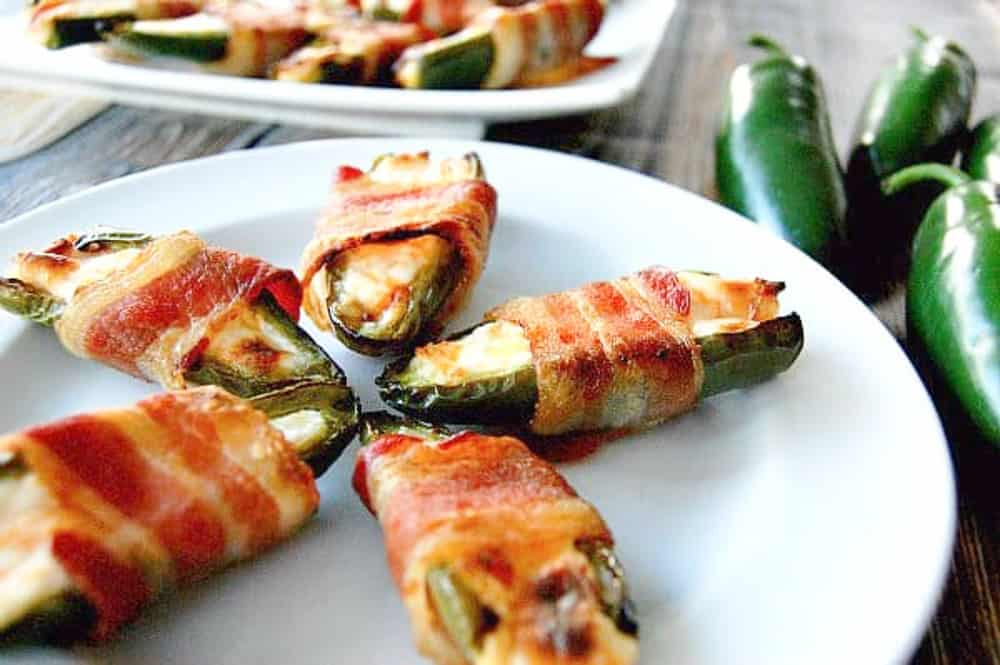 bacon wrapped jalapeno bites on a white plate.