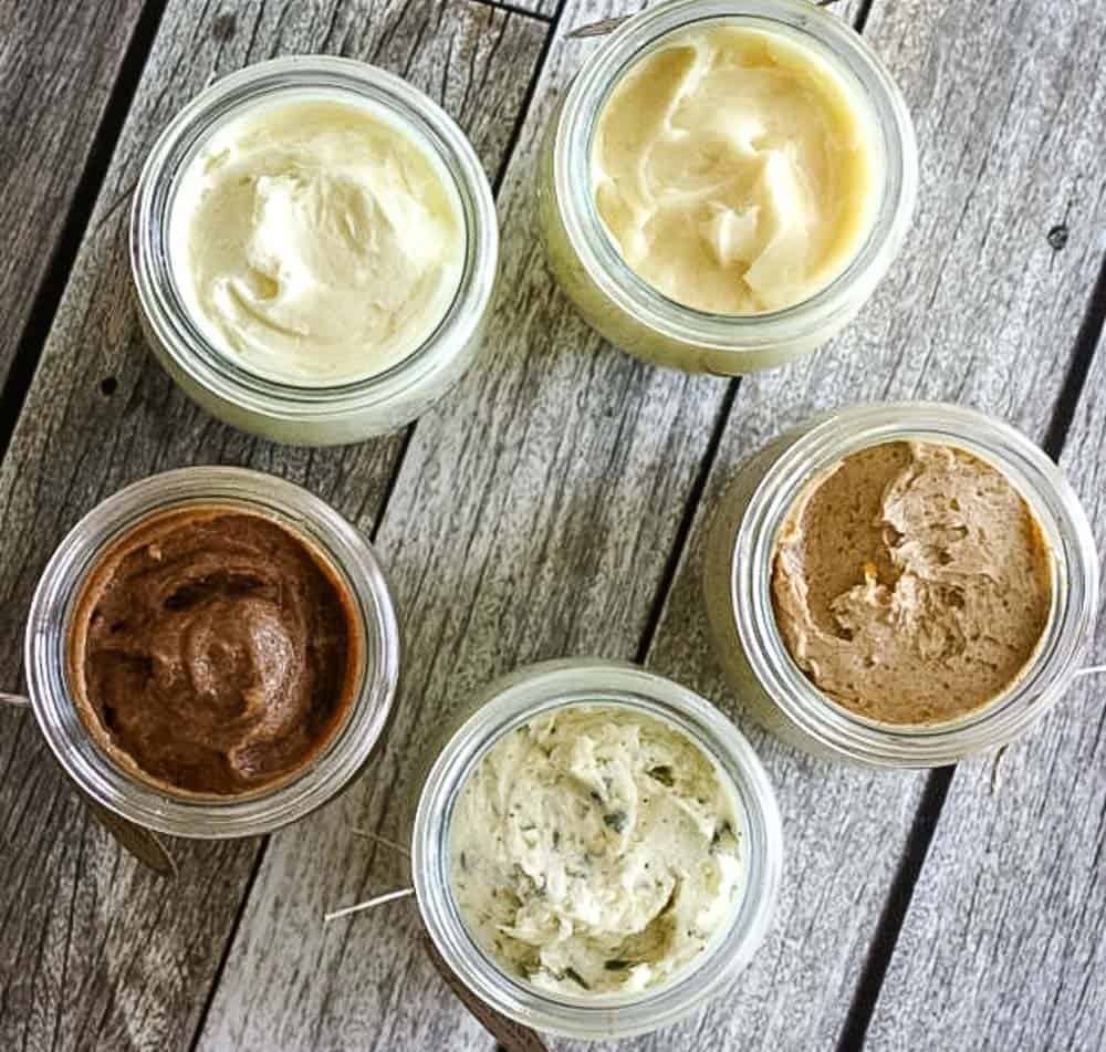 5 jars of various flavored butters on a wooden table