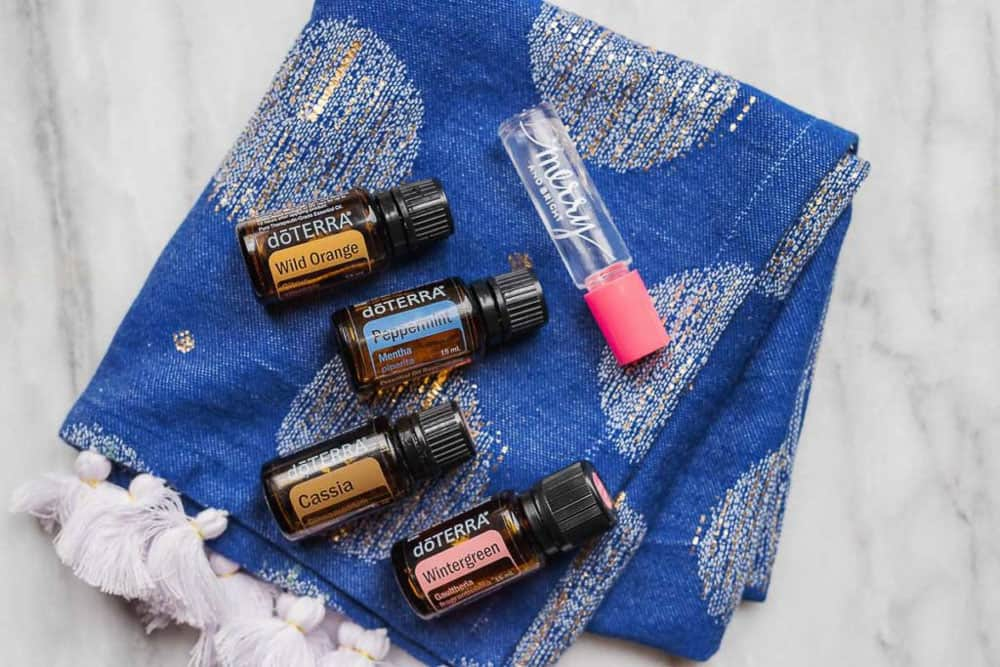 A blue decorated cloth folded up with four doTerra bottles and one Merry and Bright roll-on perfume on top of it.