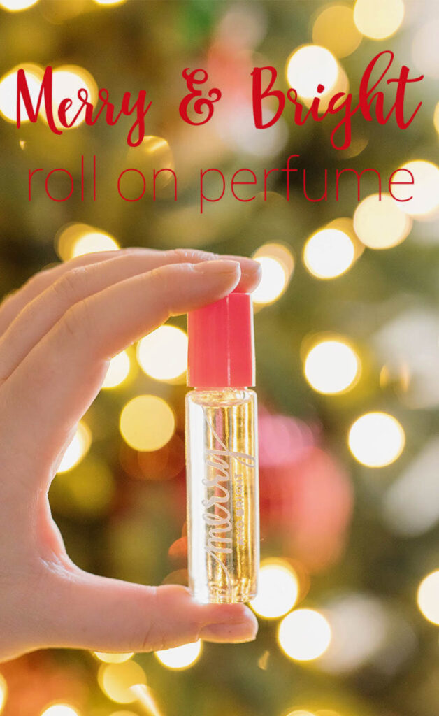 A hand holding a roll-on perfume bottle with the words Merry and Bright on it with the words Merry and Bright roll on perfume at the top.
