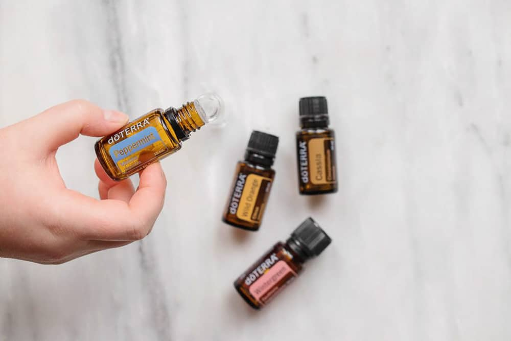 A hand holding a Peppermint DoTerra bottle with 3 Doterra bottles on the counter below.
