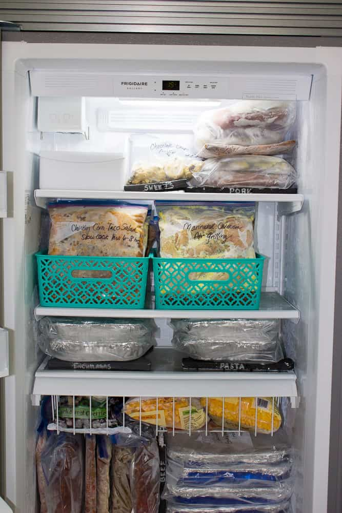 Tips to prevent freezer burn such as keeping your freezer full as shown in this image. Freezer filled with tons of freezer meals.