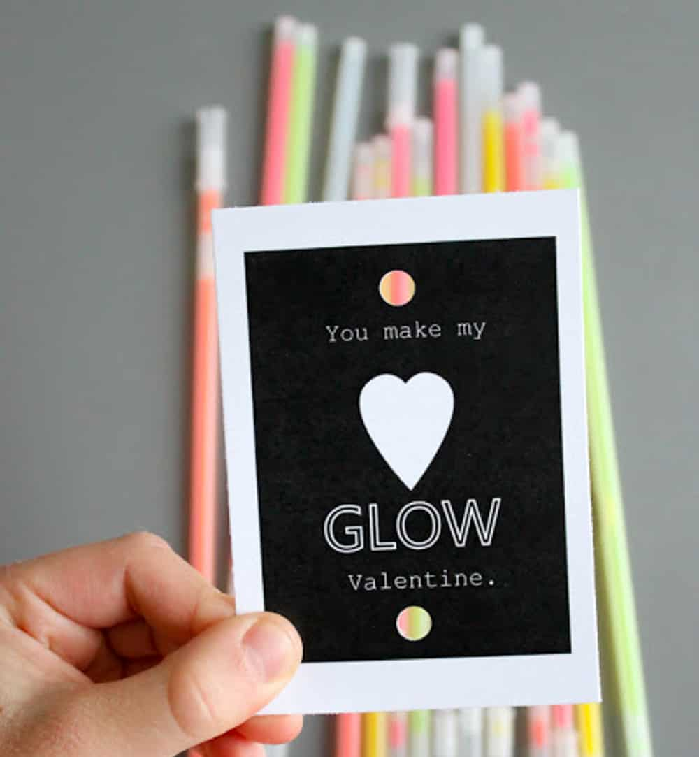 Hand holding a Valentine tag that reads You Make My Heart Glow Valentine with glow sticks in the background.