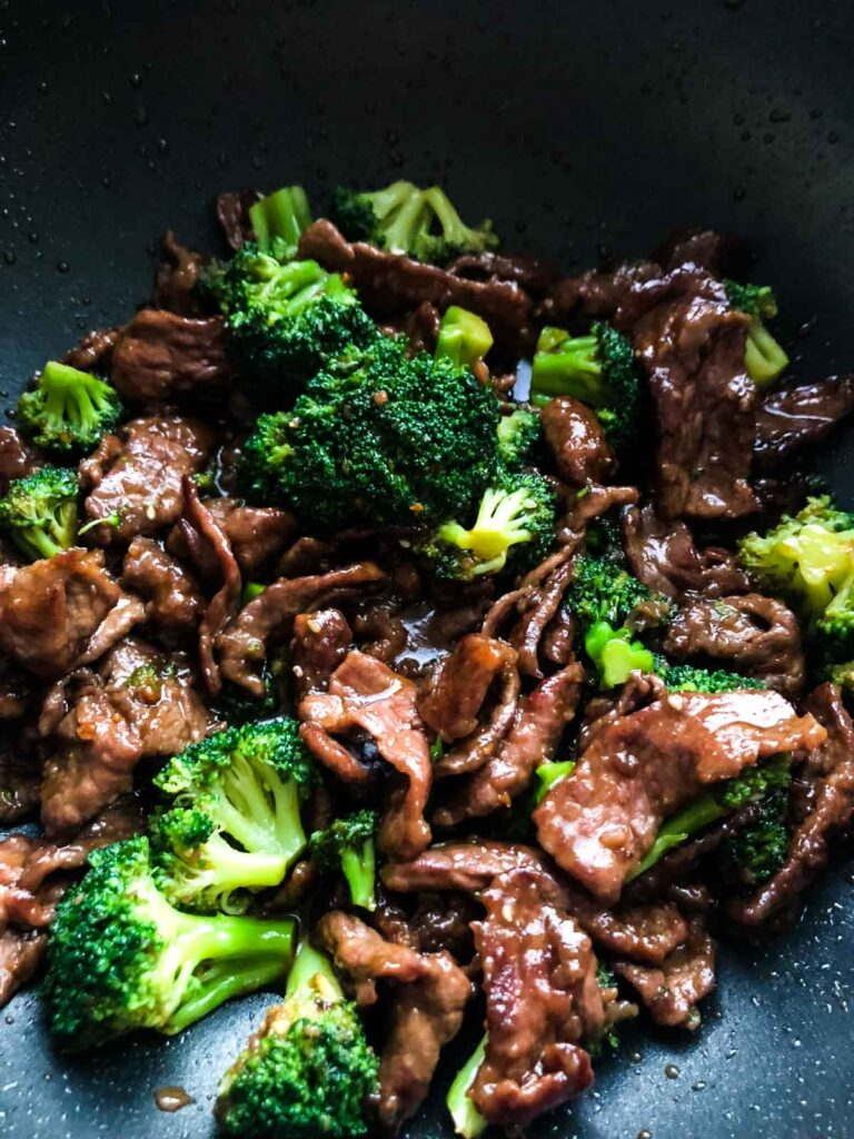 Strips of beef and broccoli cooked altogether smothered in teriyaki sauce in a nonstick pan.