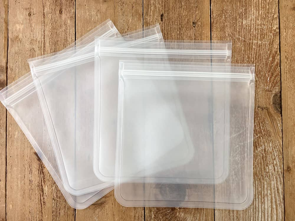 Four transparent reusable gallon sized freezer safe bags on a wood background