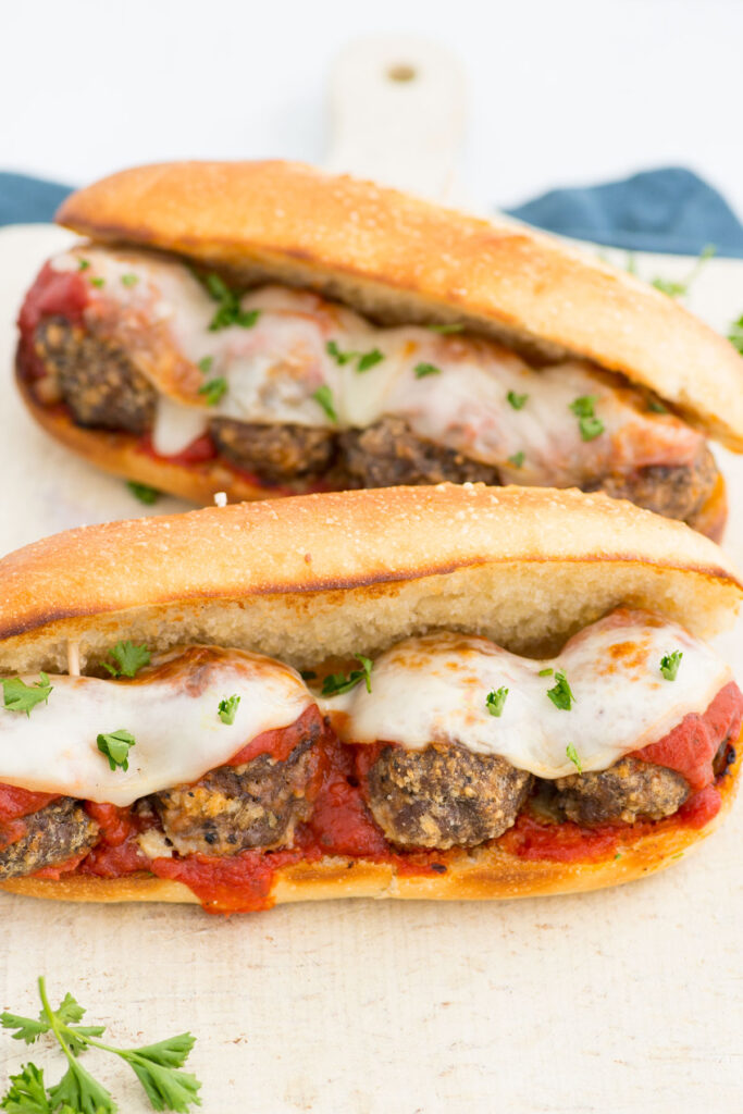 Two of this meatball sub recipe with tomato sauce, cheese, and herbs laying next to each other on a white table.