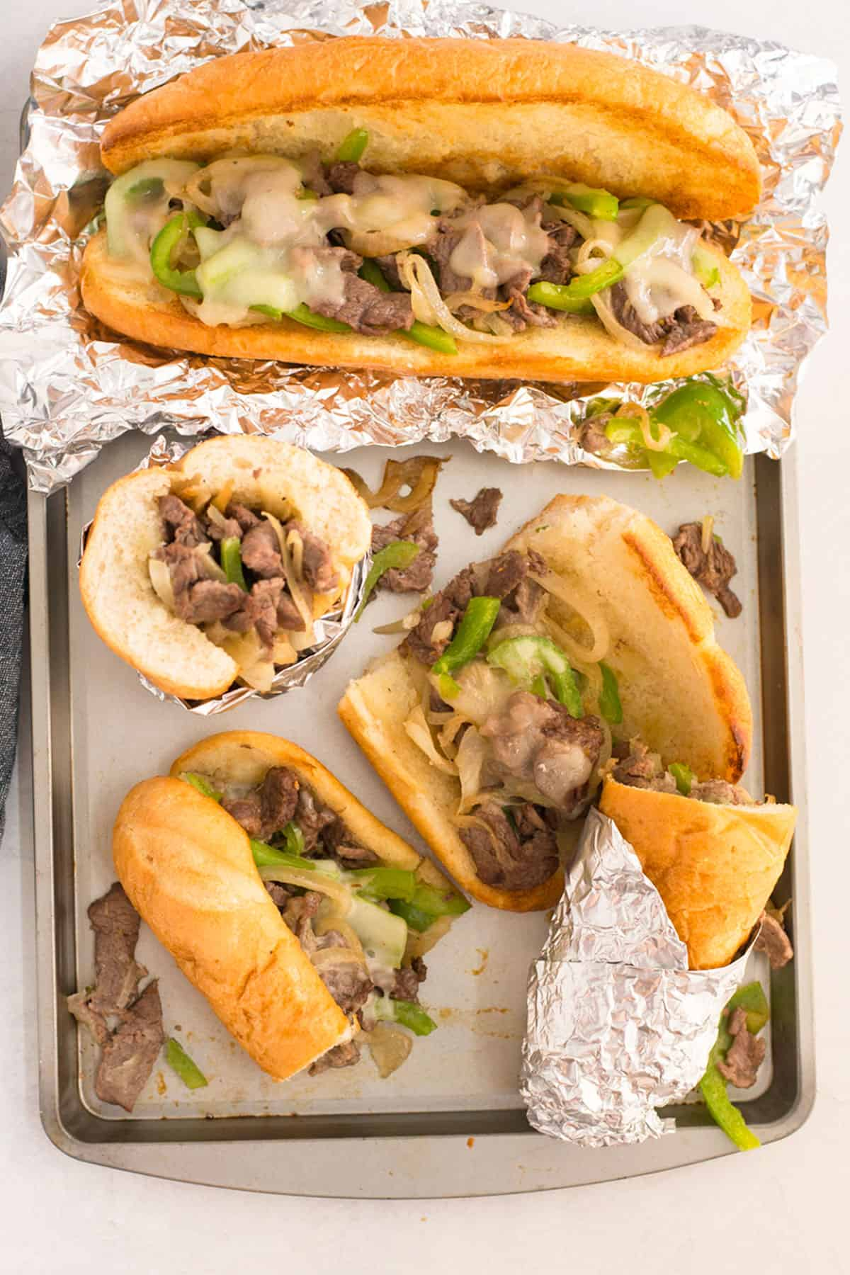 A metal pan holds a whole sandwich and four halves of a sandwich that are scattered around. Some are wrapped in foil.