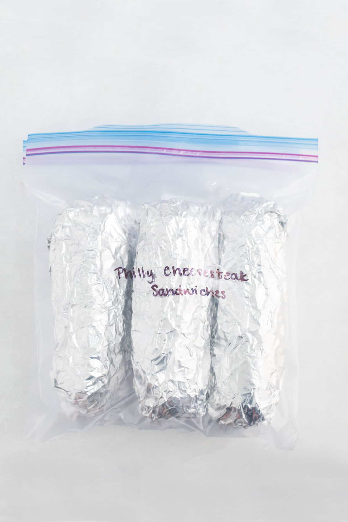 A zippered freezer bag with 6 foiled wrapped sandwiches with the words Philly Cheesesteak Sandwiches written on it with black marker.