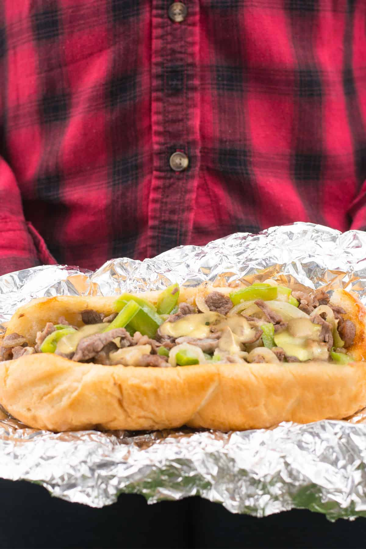 The best Philly cheesesteak recipe wrapped in foil and opened with a person wearing a red and black plaid shirt.