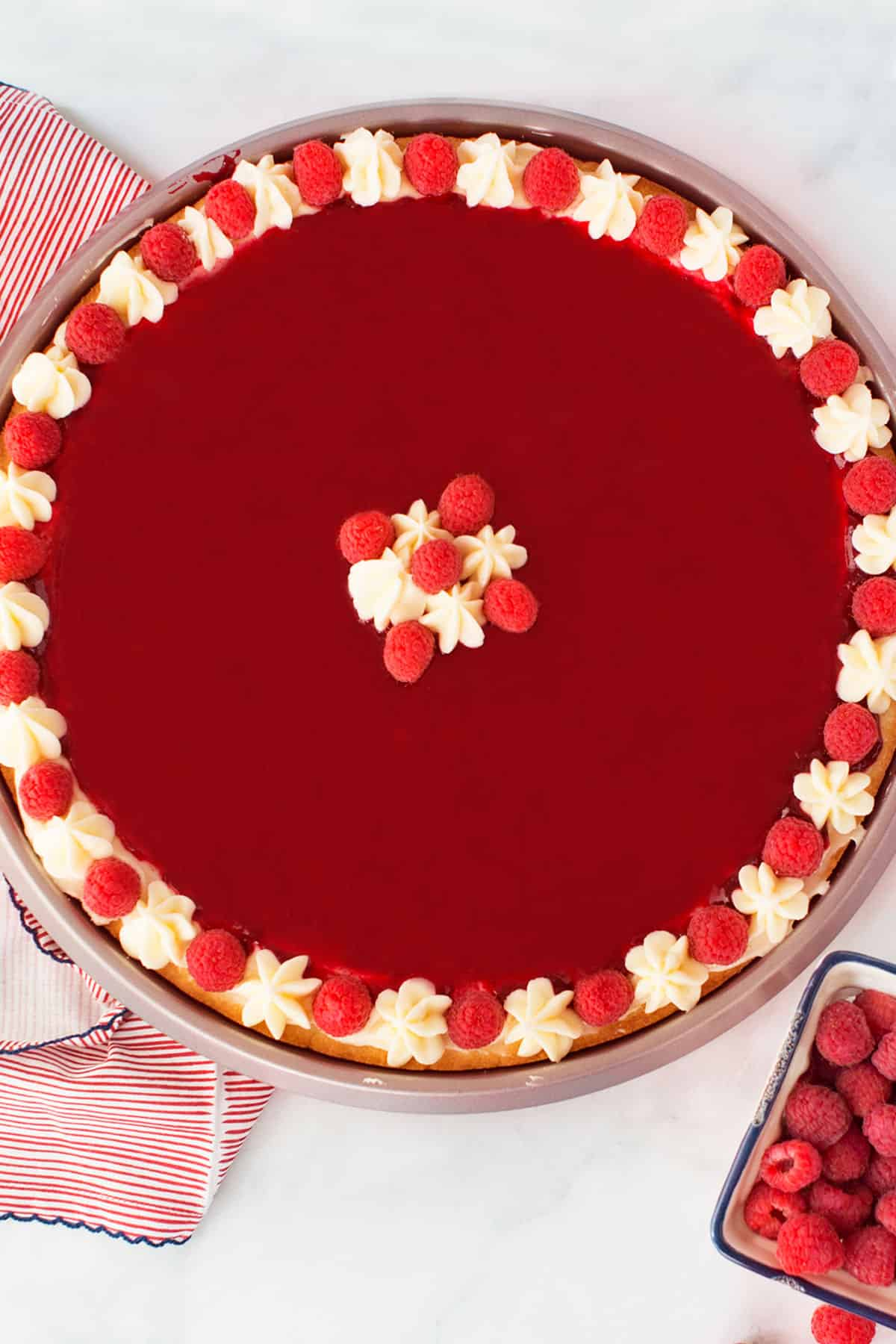 A large raspberry tart with fresh cream and raspberries on top with a red, white and blue towel and a small square dish of raspberries on the side.