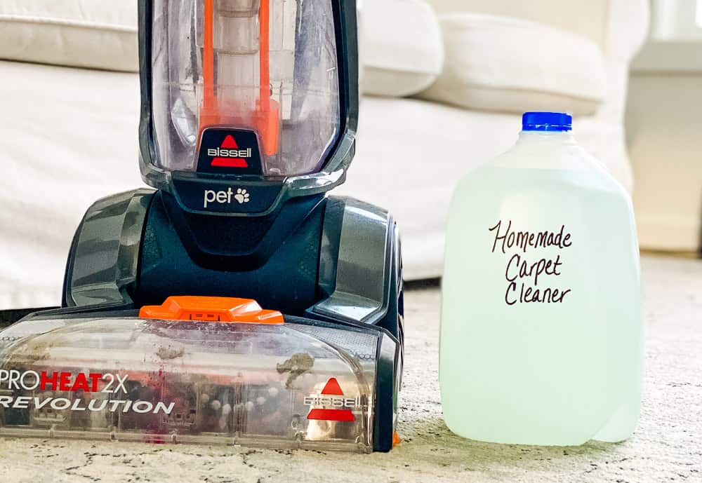 Bissell Carpet shampoo machine next to a gallon of homemade carpet cleaner solution