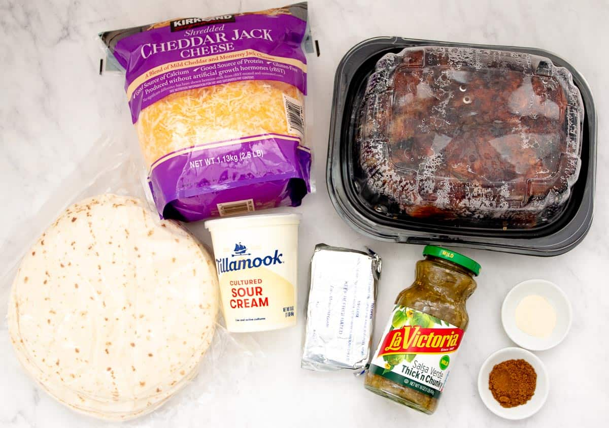 A package of tortillas, cheese, sour cream, cream cheese, a rotisserie chicken, a jar of salsa verde and two small white bowls of onion powder and cumin all lay on a white counter.