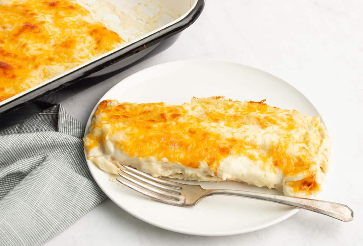 A white pan with a black rim full of cheesy chicken enchiladas with a white plate of two enchiladas with a silver fork on the plate.