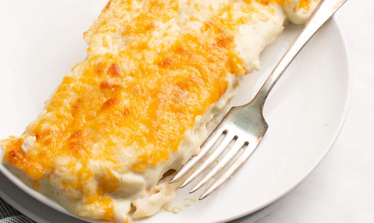 Two enchiladas covered in cheese on a white plate with a silver fork.