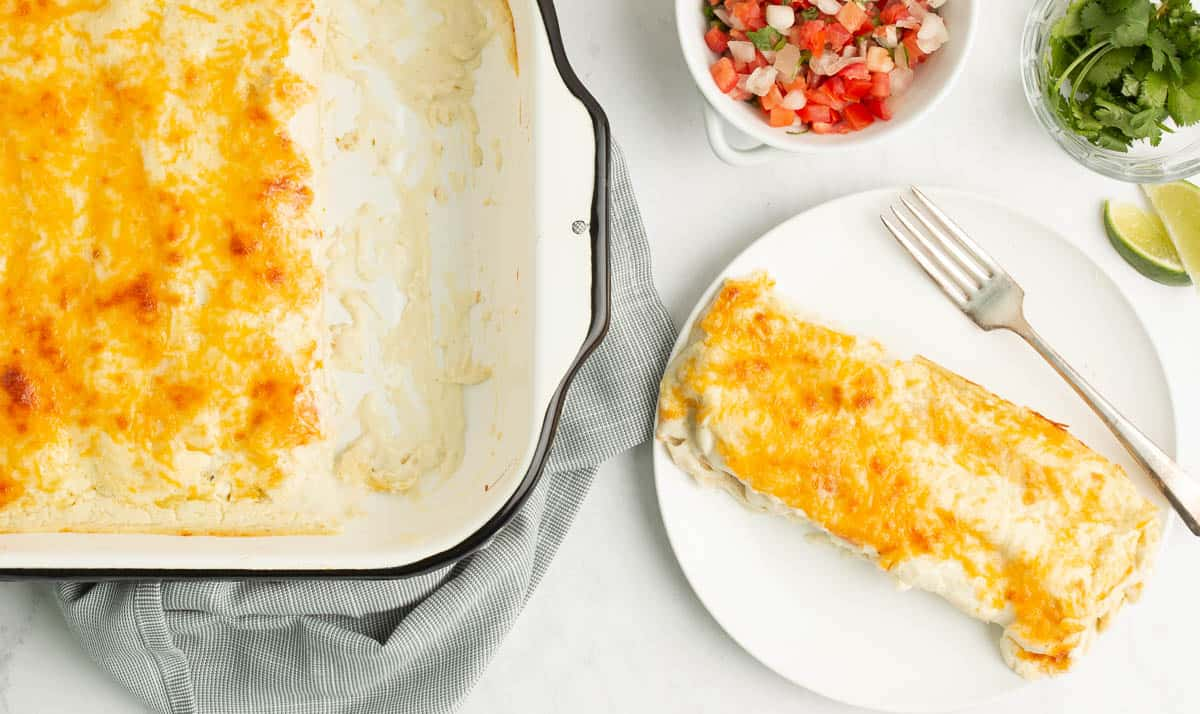 A white pan with a black rim of cheesy enchiladas with two taken out of the pan and placed on a white plate of two cheesy enchiladas with a silver fork on the plate. There are small bowls of salsa, cilantro and two limes surrounding it.