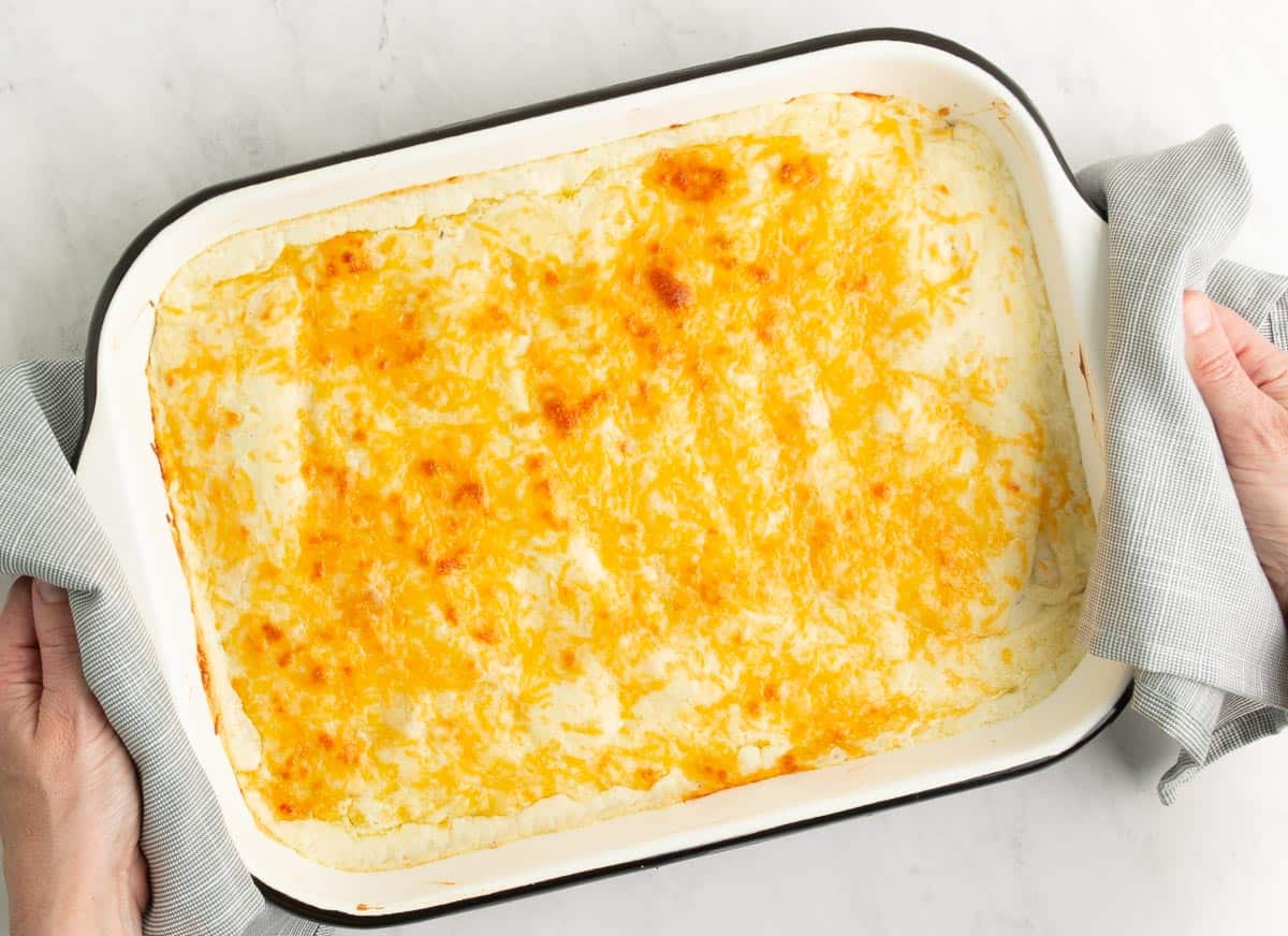 A white pan with a black rim full of cheesy enchiladas with two hands holding the two sides with a grey towel.