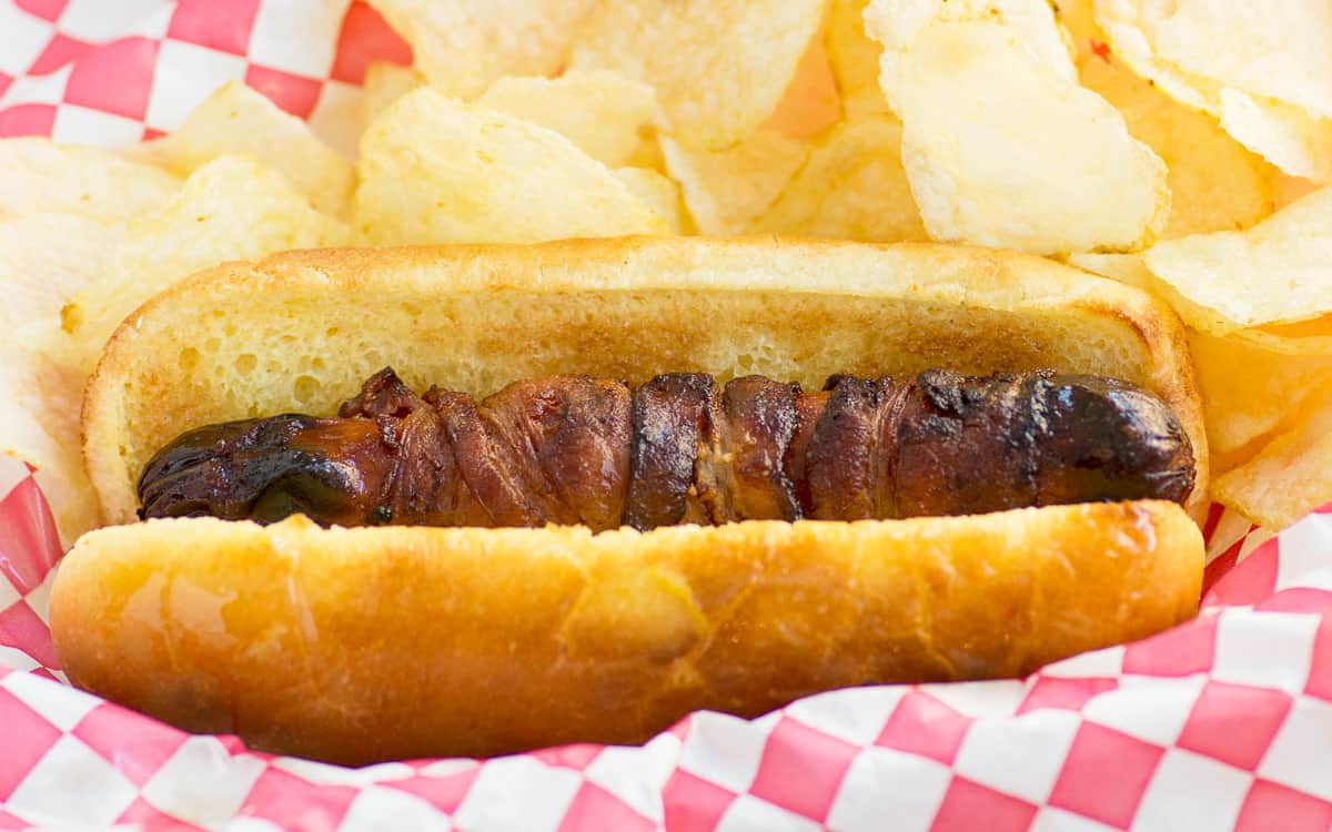 A bacon wrapped hot dog with potato chips on the side over a red and white checked paper.