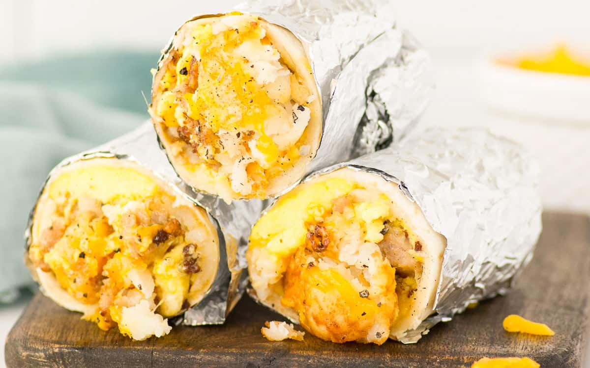 3 foil-wrapped breakfast burritos piled on top of each other on a wooden board.