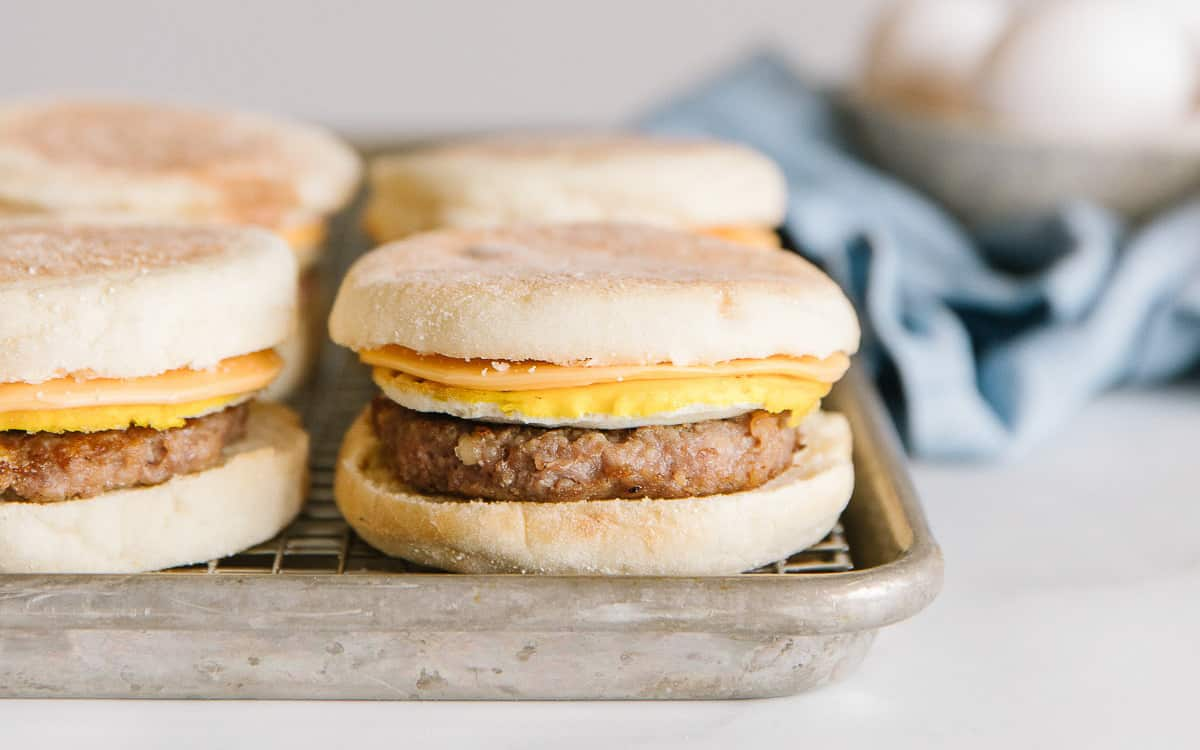 A cookie sheet holds four sausage mcmuffin breakfast sandwiches.