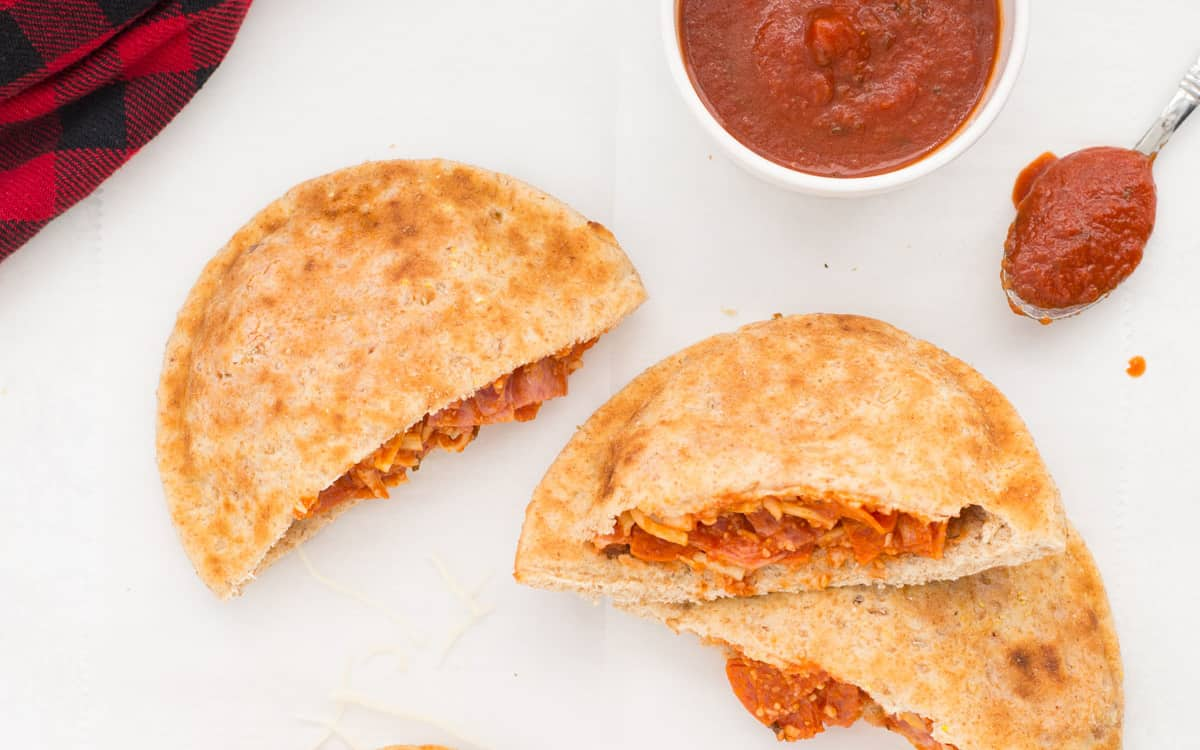 Three halves of pizza pockets with a cup of  marinara on the side.