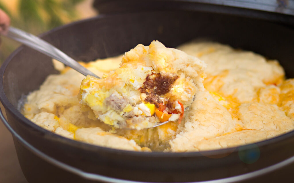 A dutch oven filled with a sausage, eggs and potatoes topped with biscuits.