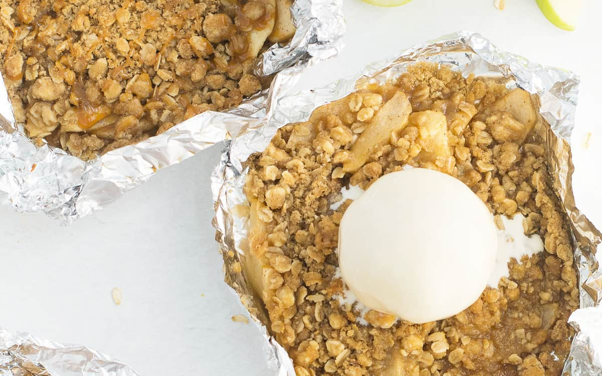 A foil packet filled with warm apples and a cinnamon crumb topping with a scoop of ice cream on it with 2 other foil packets of warm apples and a cinnamon crumb topping above and below it. There is a green apple and cinnamon sticks laying beside it too.