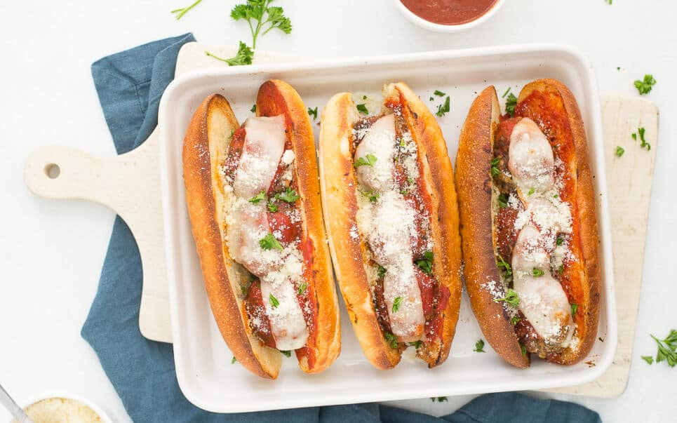 A white cutting board with a white serving platter holding three meatball sandwiches.