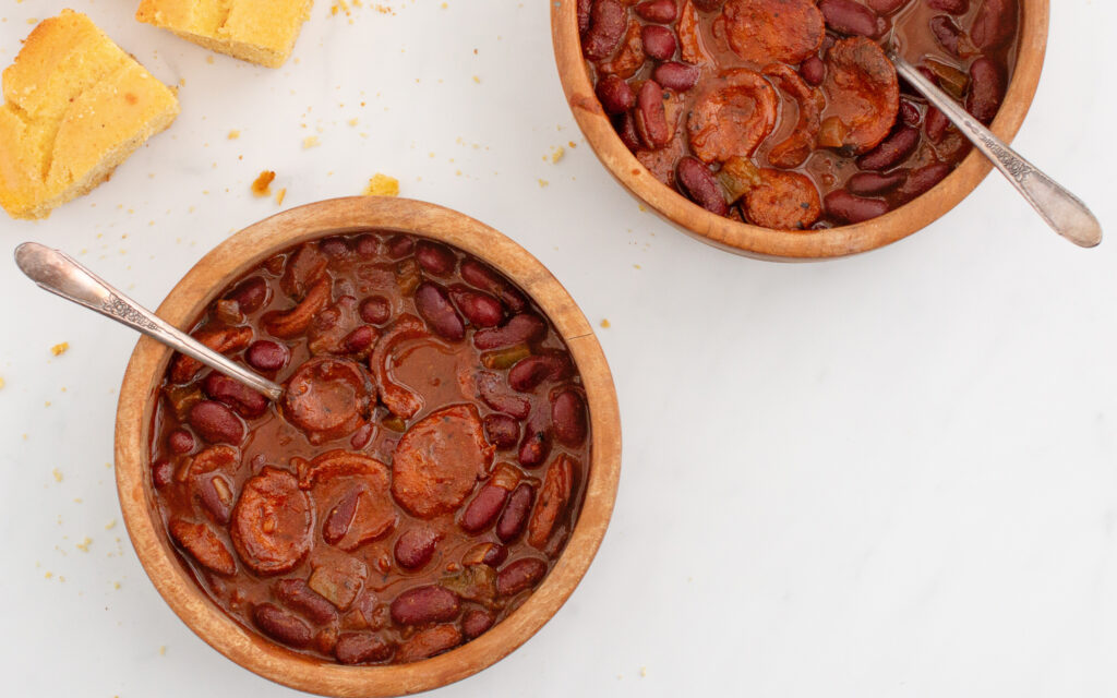 Two wooden bowls of chili with metal spoons in it and a piece of cornbread on the side for a good make ahead camping meals.