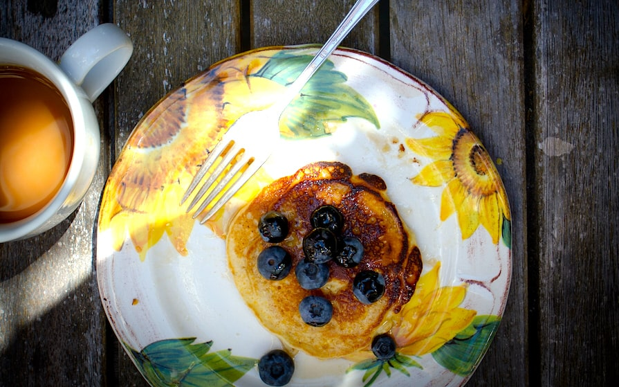 A flowered plate on a picnic table with one pancake with blueberries on it with a fork on the plate and a cup of coffee on the side.